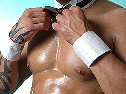 A mans hands adjusting his black bowtie, whilst dressed as a butler in the buff and wearing white cuffs