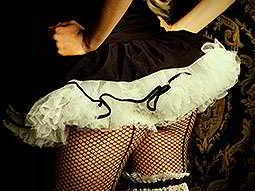 The back of a woman in a black and white tutu, corset and fish nets