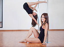 A woman upside down on a pole in the background, with a woman sat against a pole in the foreground