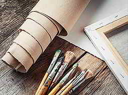 An artists paint brushes and canvas laid out on a wooden table