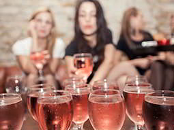 Close up on glasses of rose wine in the foreground, with women sat in the background
