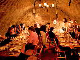 The interiors of a restaurant, within an underground vault, with lots of people eating there