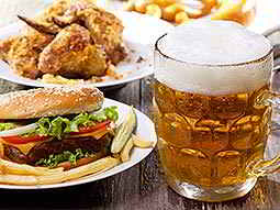 Some beer in a stein with some chicken and a burger