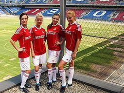 Four girls wearing football kits, in a football stadium
