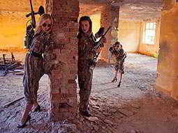 Some women in camouflage holding guns and hiding around a brick column