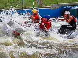 Three people sat in a raft on a white water course