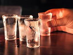 A mans hand holding a shot of vodka, with three other shots in the foreground