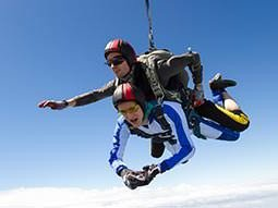 A man skydiving with another man on his back, to a backdrop of the sky