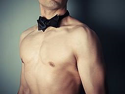 A naked mans torso in a black bowtie