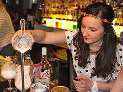 A woman pouring a cocktail into a glass
