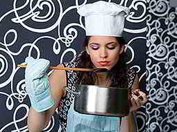 A woman in a white chef hat and blue oven gloves, holding a pan and tasting from a wooden spoon