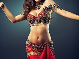 A woman dressed in a red Bollywood outfit, dancing