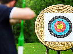 The back of a man not in focus, aiming at a colourful archery target