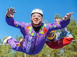 Close up of a man in a purple skydiving suit, freefalling on an outdoor simulator