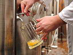 Close up of a mans hands pouring out beer into a stein