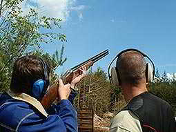 The back of a man aiming to the sky with a shotgun, with an instructor stood to the side of him