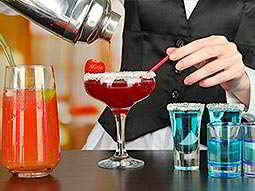 Close up of a bartender pouring out a red cocktail into a full martini glass, with blue shots on one side and an orange drink to the other side