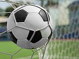 A white and black football hitting the back of a goal net
