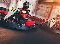 Two people in go karts, racing on an indoor track
