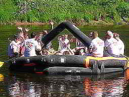 A group of guys waving from a raft in the river