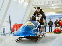 People in a blue bobsleigh at the top of a track, with a man stood behind and pushing them
