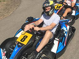 A man sitting in a go kart with a helmet on