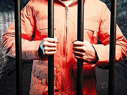 A mans torso in an orange prisoner suit, stood in a prison cell and holding onto the bars