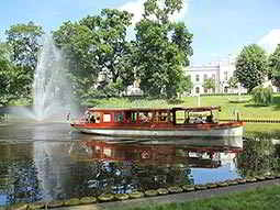 A small river boat on the river with a grand building in the background on the banks of the river