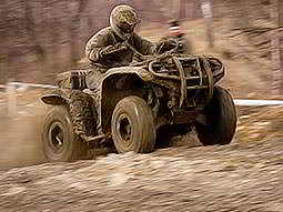 A man driving a quad bike through the wilderness