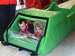 Two men in a green skeleton bobsleigh