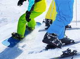 Close up of people in colourful ski suits, with one man on a snowboard and two others on skis