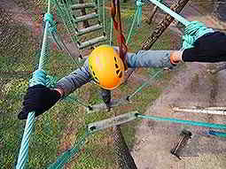 Birds eye view of a person crossing a rope bridge outdoors in a yellow helmet
