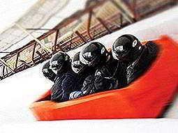 The back of five people sat in a red soft bobsleigh on an ice track