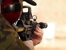 A person aiming a sub-machine gun away