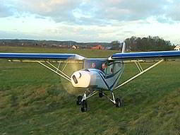 A light aeroplane on green grass with its propeller spinning
