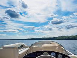 A view of still water and a coastline from the driving seat of a boat
