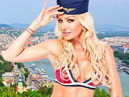 A woman wearing underwear and a pilots hat, saluting against a background of a river city