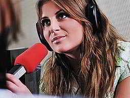 A woman wearing headphones and leaning towards a red microphone
