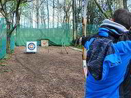 a man firing an arrow into the distance at a target