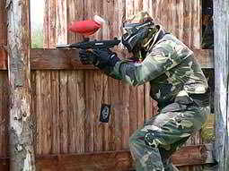 A man wearing camouflage and aiming his gun through a gap in a wooden fence