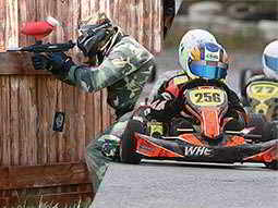 A split image of a man aiming his gun through a hole in a fence and some people driving go karts around a track