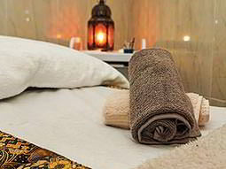 A rolled up brown towel on a massage bed