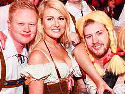 A blonde woman in a Bavarian Beer Maid outfit, posing with two men in Bavarian outfits and one in a blonde pigtail wig
