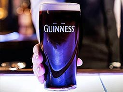 A man's hand holding a pint of Guinness