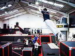 A man jumping in the air above black obstacle boards