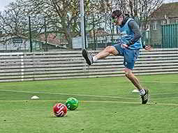 A man in a blue sport bib and wearing goggles, attempting to kick two footballs on an outdoor pitch