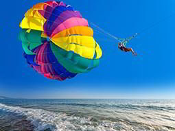 A person attached to a colourful parachute whilst paragliding above the sea