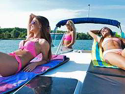 Three women sunbathing in bikinis on the front of a boat