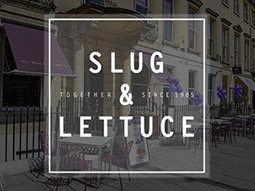 The exterior of a Slug and Lettuce bar, with outdoor seating and purple awnings