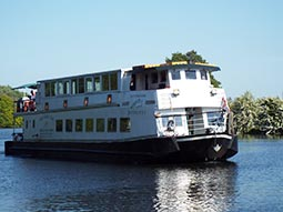 A long white pleasure boat with glass windows